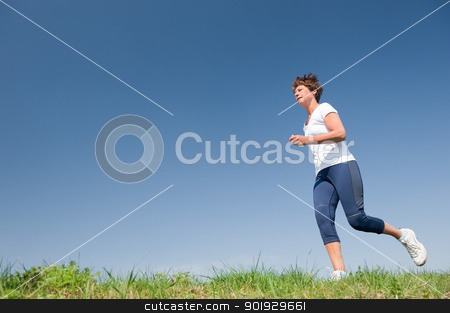 Running senior woman stock photo, Active senior woman is running (jogging) in front of blue sky by Picturehunter