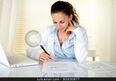 Charming businesswoman working at office stock photo, Charming businesswoman working at office in front of her laptop by pablocalvog