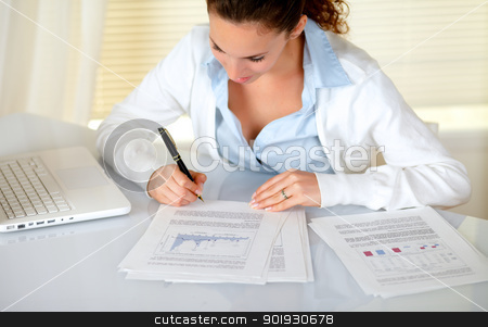 Charming businesswoman reading documents stock photo, Charming businesswoman reading documents at workplace in front of her laptop by pablocalvog