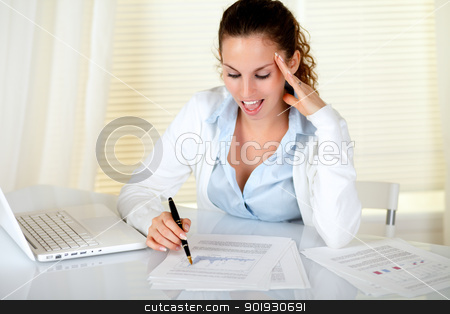 Surprised businesswoman reading documents stock photo, Surprised businesswoman reading documents in front of laptop at workplace by pablocalvog