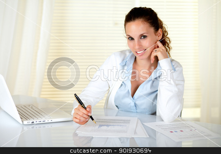 Adult caucasian secretary looking at you stock photo, Adult caucasian secretary looking at you while working with documents and laptop by pablocalvog