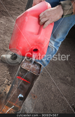 Special Effects Worker Pouring Gasoline stock photo, Special effects worker pours gasoline into canister for detonation device by Scott Griessel