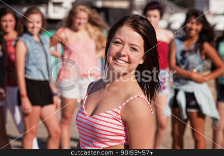 Upbeat Teenage Girl Smiling stock photo, Upbeat Caucasian female teenager with smile near group of people by Scott Griessel