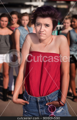 Sad Girl with Hunched Shoulders stock photo, Lonely girl with hunched shoulders near group of people by Scott Griessel