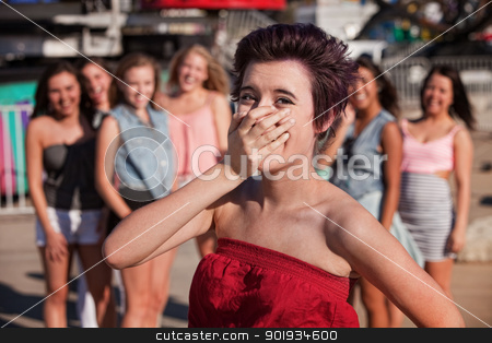 Laughing Teenage Girl Covers Her Mouth stock photo, Female Hispanic teenager covering her mouth while laughing by Scott Griessel