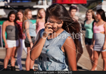 Shy Teenage Girl Looking Down stock photo, Shy teenage Filipino girl looking down with friends nearby by Scott Griessel