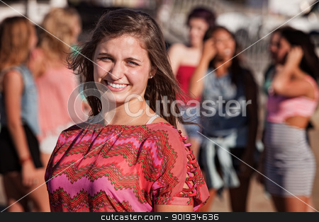 Smiling Teenage Girl Outside stock photo, Smiling young European girl with friends in the background by Scott Griessel