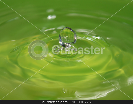Water drop stock photo, The green drop of water falls leaving circles on a surface being reflected and sparkling by aarrows