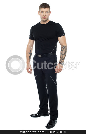 Strong male bouncer. Tattoo on both his hands stock photo, Strong male bouncer. Tattoo on both his hands. Full length shot by Ishay Botbol