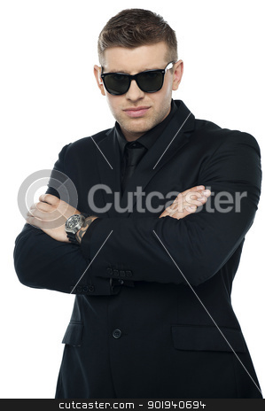 Young stylish bouncer in a black suit, arms folded stock photo, Young stylish bouncer in a black suit, arms folded. Half length portrait by Ishay Botbol