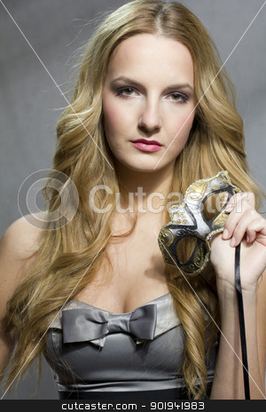 Woman holding a mask stock photo, Young woman holding a venecian mask at valentine's day by Peter Mikuska