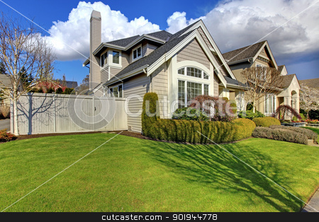 Classic American house with fence and green grass during spring. stock photo, Classic American house with fence and green grass during spring. by iriana88w