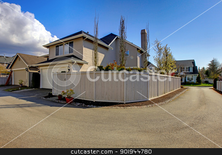 Beige house from backyard with garage and fence near road. stock photo, Beige house from backyard with garage and fence near road. by iriana88w