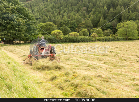 Antique tractor and threshing machine stock photo, Antique tractor and threshing machine turns hay by Buttermere in English Lake District by Steven Heap