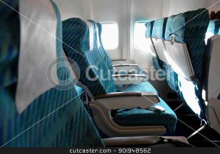 Airplane seat row stock photo, row of blue seats indoors in passenger airplane by Julija Sapic