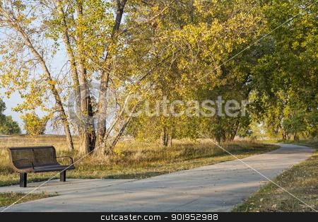 recreational biking trail stock photo, bench and recreational biking trail in Boyd Lake State Park near Loveland, Colorado, fall scenery by Marek Uliasz