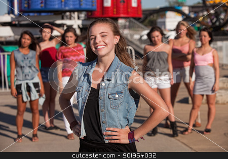 Smiling Girl with Hand on Hips stock photo, Happy blond teen with big smile in front of friends by Scott Griessel