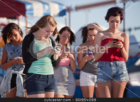Young Ladies Using Their Phones stock photo, Young woman at amusement park using their phones by Scott Griessel