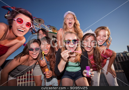 Group of Girls Blowing Bubbles stock photo, Laughing teenage girls blowing bubbles at an amusement park by Scott Griessel