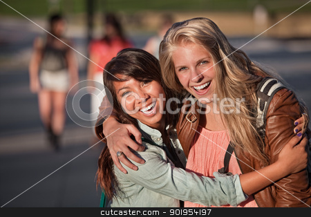 Two Young Women Laughing stock photo, Two laughing female students hugging each other outdoors by Scott Griessel