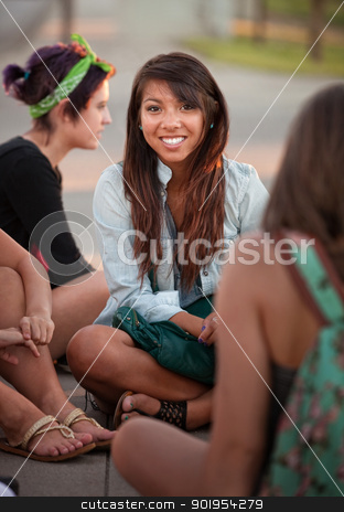 Pretty Teenage Girls Sitting on the Ground stock photo, Grinning Filipino girl with friends sitting cross legged  by Scott Griessel