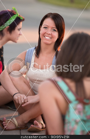 Cute Teen Girl Outside stock photo, Cheerful Caucasian teen sitting on the ground with friends by Scott Griessel