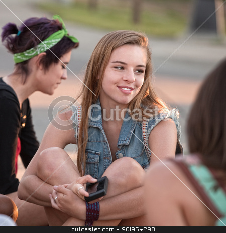 Pretty Teen Holding Phone stock photo, Pretty young teenage girl holding phone and smiling by Scott Griessel