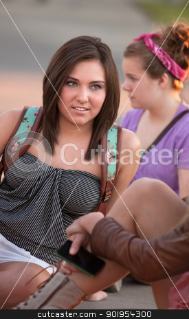 Teenager Listening to Friends stock photo, Caucasian female teenager listening to friends sitting on the ground by Scott Griessel