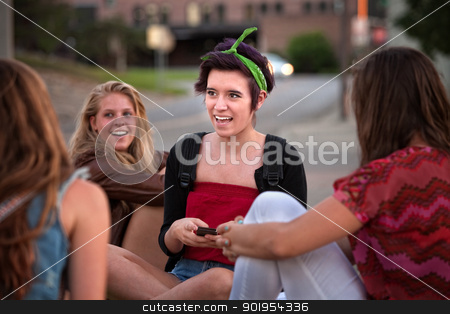 Teen Girls Texting Messages stock photo, Hispanic female teenager with friends sitting on the ground by Scott Griessel