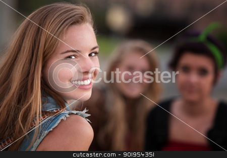 Smiling Teen Girl with Two Friends stock photo, Smiling teenage girl with pair of female friends outdoors by Scott Griessel