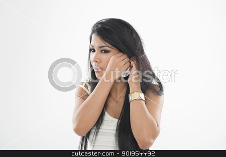 Woman putting on her earring stock photo, Attractive Asian woman putting on her large decorative silver earring isolated on white by Instudio 68
