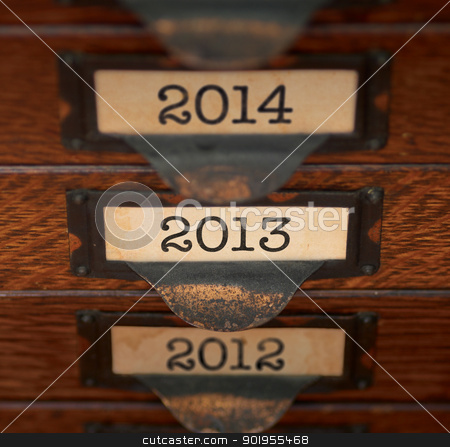 Retro Focus on 2013 stock photo, Stack of old, oak flat file drawers with years 2012, 2013, and 2014 printed on tags in tarnished brass label holders. Shallow DOF with focus on 2013. by Mark Carrel