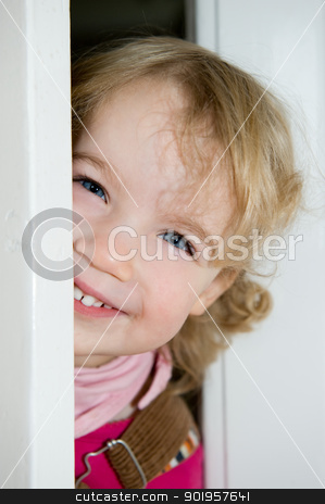 Smiling little girl stock photo, Smiling young girl behind a door by Picturehunter