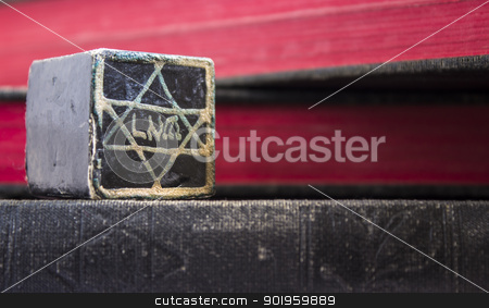 Black Tefillin Cover stock photo, A black tefillin cover with black and red books in the background. by Jadthree