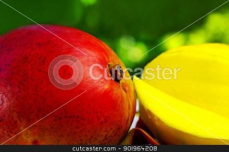 Sliced mango on green background stock photo, Sliced mango on green background by Inacio Pires