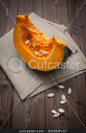 Pumpkin slice stock photo, Pumpkin slice on dark wood table by Giordano Aita