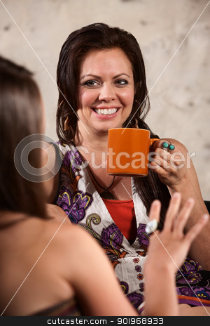 Smiling Woman Drinking Coffee with Friend stock photo, Happy Caucasian brunette drinking coffee and talking with friend by Scott Griessel