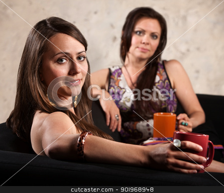 Pretty Women Relaxing on Sofa stock photo, Pretty European woman looking over her shoulder with friend behind her by Scott Griessel