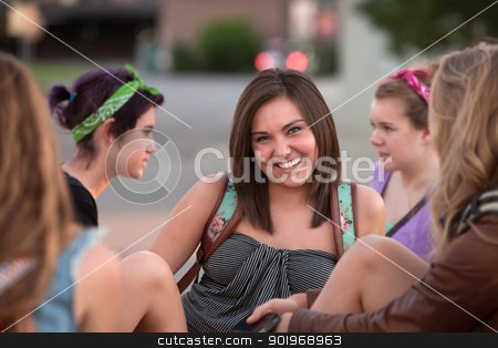Cheerful Caucasian Student stock photo, Cute Caucasian student with smile sitting among friends by Scott Griessel