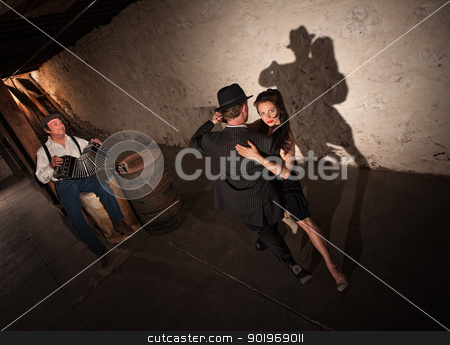 Young Tango Dancers Performing stock photo, Tango dancers performing indoors with squeezebox player in background by Scott Griessel