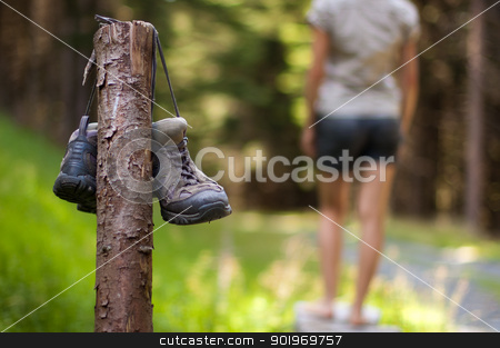 Abandoned hiking shoes stock photo, Abandoned hiking shoes with a woman walking bare feet  by kamsta