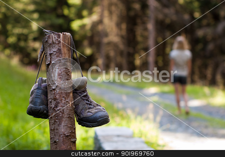 Abandoned hiking shoes stock photo, Abandoned hiking shoes with a woman walking bare feet  by Kamila Starzycka