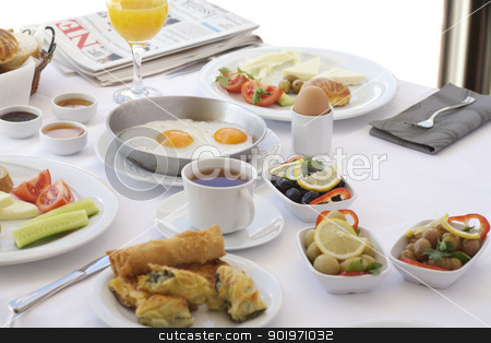 Breakfast table with tomatoes, cucumber, cheeses and olives stock photo, Fresh orange juice and tea on breakfast table with tomatoes, egg, cucumber, cheeses and olives by necati turker