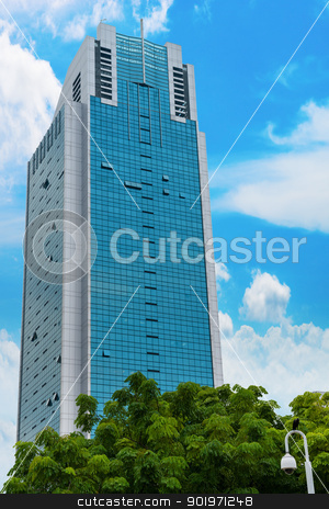 Skyscraper with blue sky and and green trees stock photo, Skyscraper with blue sky on background and trees on front by Iryna Rasko