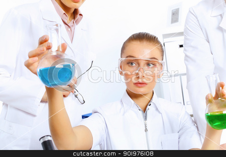 Young female scientist working in laboratory stock photo, Young female scientist working with liquids in laboratory by Sergey Nivens