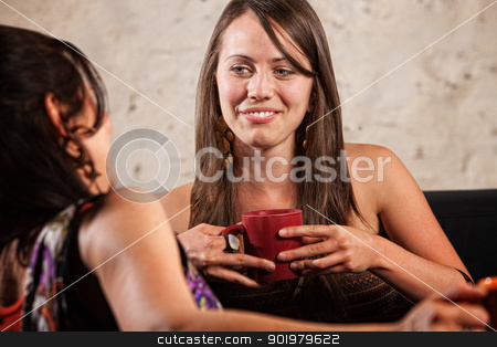 Pretty Brunette Talking with Friend stock photo, Caucasian female holding coffee cup and talking with friend by Scott Griessel