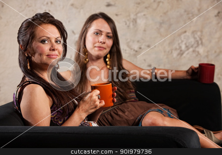 Smiling Calm Women Sitting stock photo, Smiling calm pair of women sitting on sofa holding coffee mugs by Scott Griessel