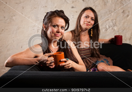 Satisfied Coffee Drinkers on Sofa stock photo, Two cute young white women grinning on sofa with coffee mugs by Scott Griessel