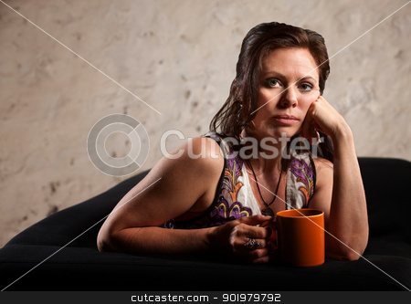 Serious Woman with Hand on Cheek stock photo, Beautiful serious European brunette female with coffee mug by Scott Griessel