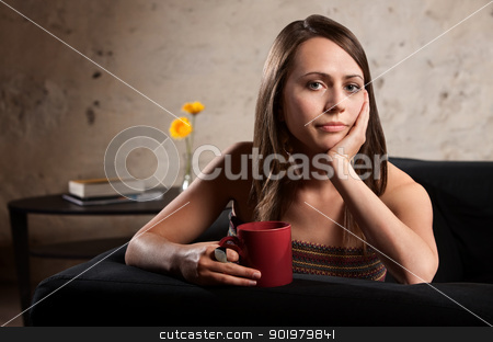 Serious Woman with Hand on Cheek stock photo, Pensive European woman holding cup with hand on cheek by Scott Griessel